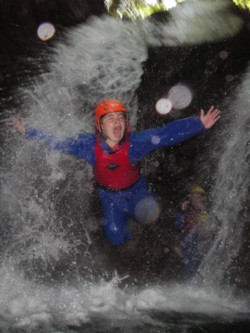 Ghyll scrambling jumping in from under the waterfall Coniston